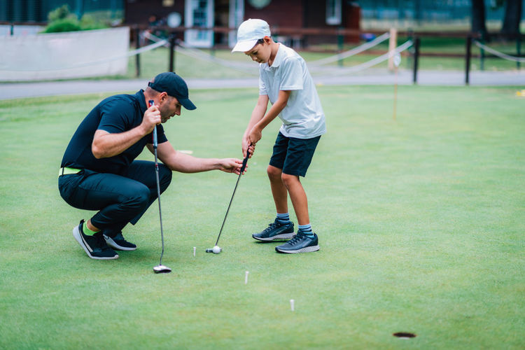 Full length of men playing on golf course