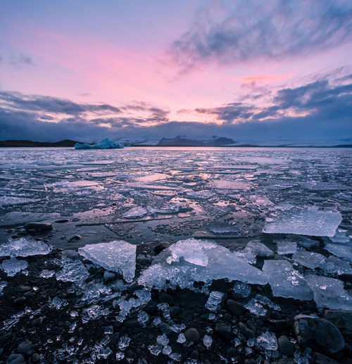 Colorful sunset landscape in Jokulsarlon glacier lagoon in Iceland with ice chunks and mountains Landscape Beauty In Nature Beautiful Colorful Jökulsárlón Jökulsárlón Glacier Lagoon Water Sea Sunset Beach Wave Low Tide Frozen Water Awe Sky Iceberg - Ice Formation Glacier Iceberg Glacial Lagoon Ice Iceland Visual Creativity