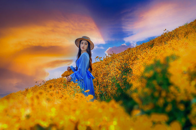 Woman standing on yellow flowering plant against sky during sunset