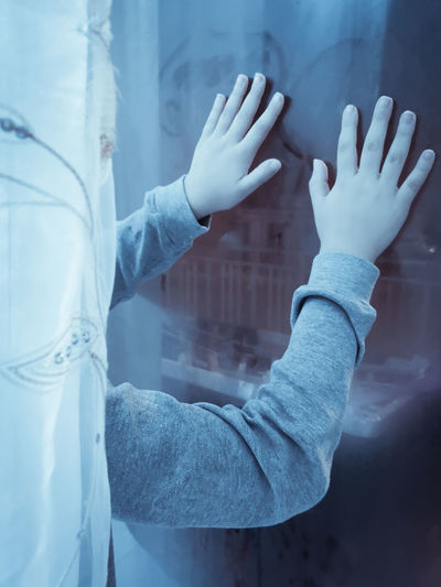 Cropped hands of person on glass window