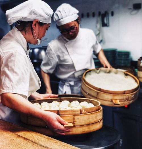 Chefs preparing dumplings in kitchen