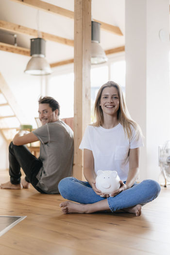 Young couple sitting on wooden floor