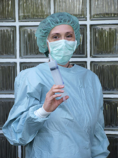 Portrait of healthcare worker holding syringe