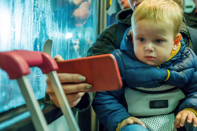 Young happy mother holding baby while he pulls her hair while travelling by train Travel Baby Babyhood Bus Care Child Childhood Cute Digital Front View Gadget Holding Indoors  Innocence Looking Men People Portrait Real People Sitting Smartphone Three Quarter Length Two People Young A New Beginning