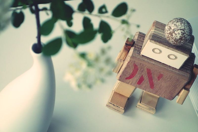 High angle view of wooden robot by white vase