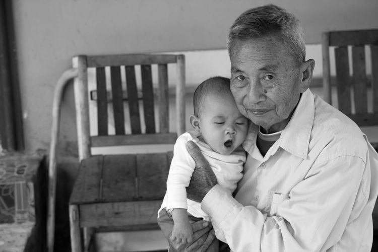 Portrait Of Grandfather Holding Grandson Against Bench