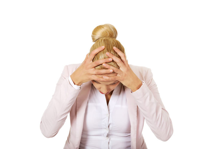 Stressed businesswoman holding her head against white background