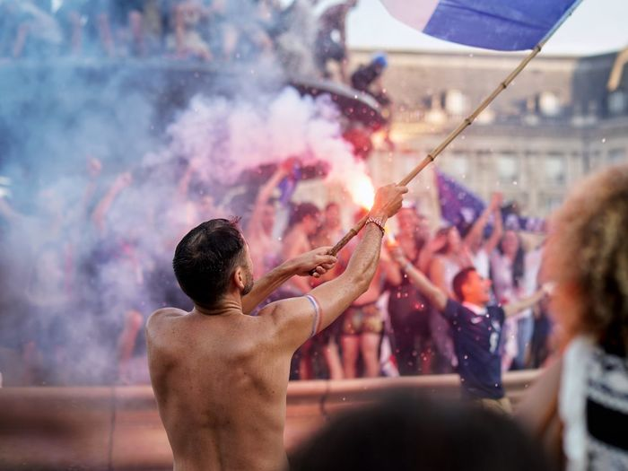 Rear view of shirtless man waving flag at music festival