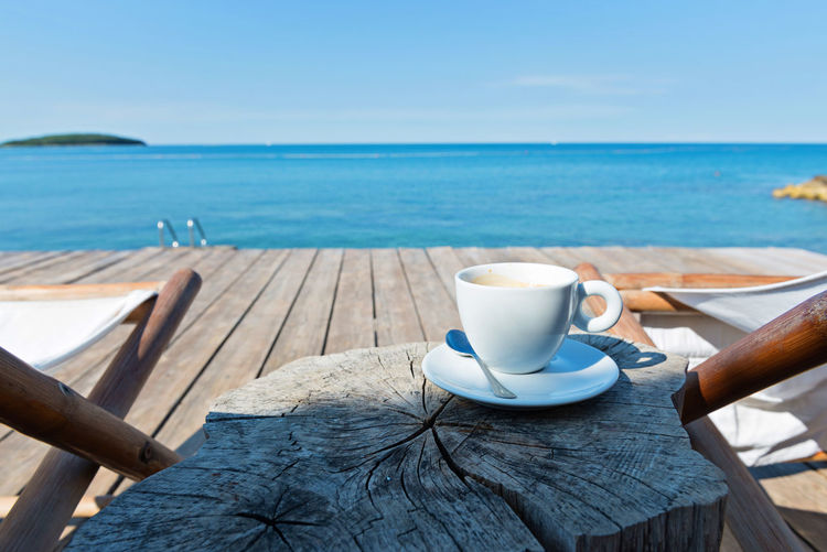 Wooden floor and sea view with chaise-longues and cup of coffee, Istria, Croatian coast Blue Breakfast Coffee Coffee - Drink Coffee Cup Crockery Cup Day Drink Food And Drink Horizon Horizon Over Water Mug Nature No People Outdoors Refreshment Saucer Sea Sky Table Water Wood - Material