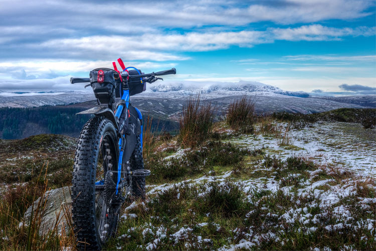 Blue Bicycle On Mountains Against Cloudy Sky At Dusk