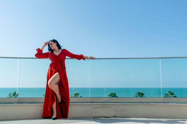Beautiful woman standing against sea and clear blue sky