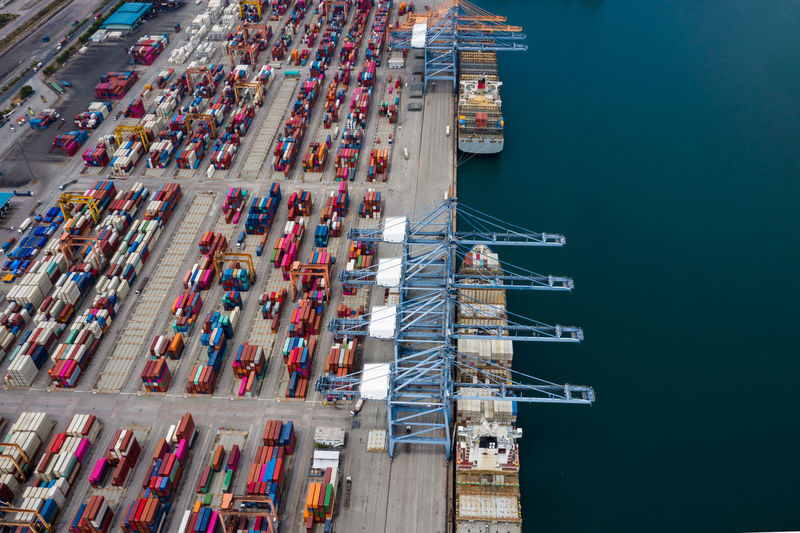 High angle view of commercial dock by pier against blue sky