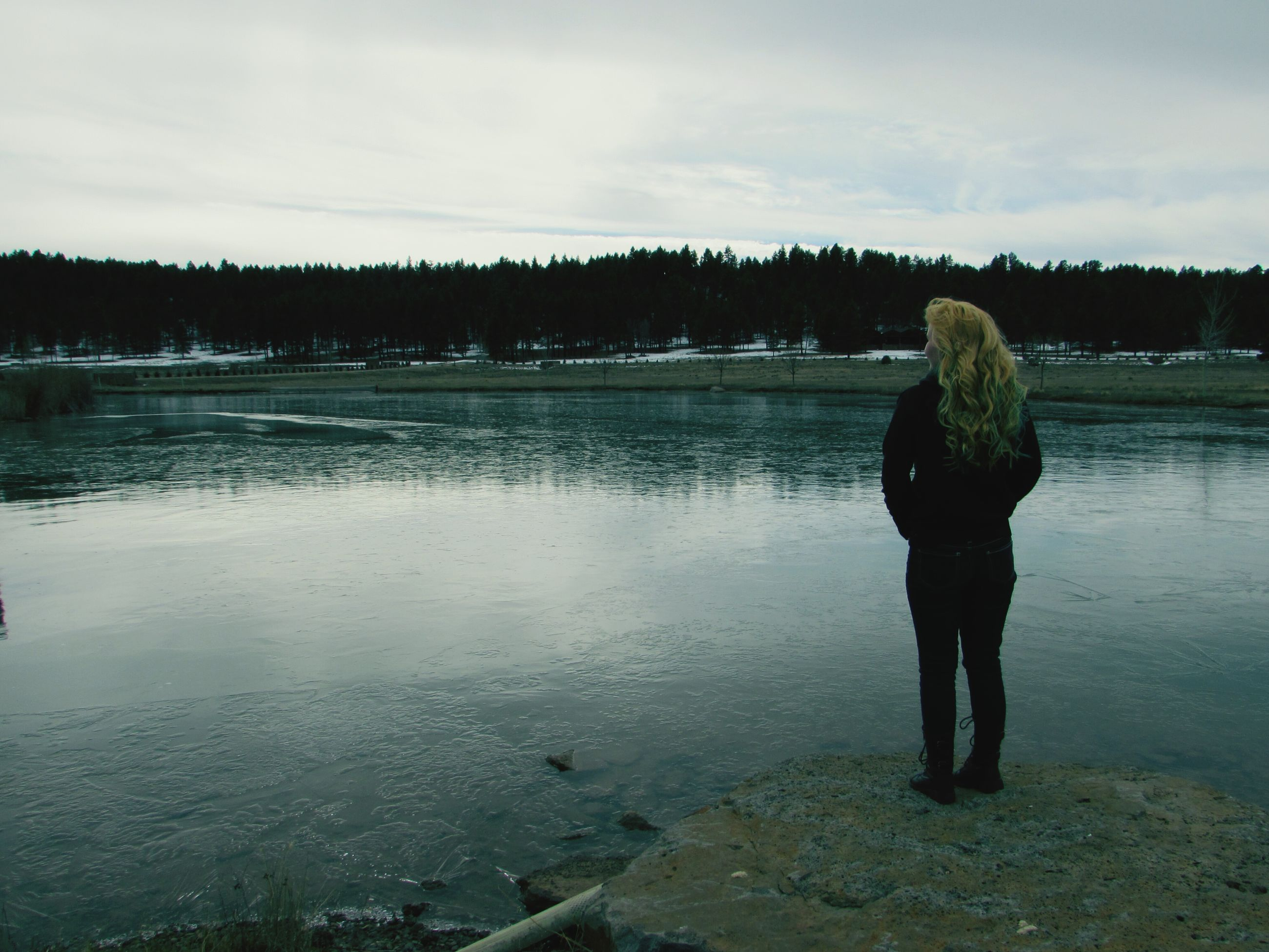 water, lifestyles, leisure activity, full length, standing, casual clothing, sky, lake, rear view, tranquility, three quarter length, tranquil scene, nature, scenics, beauty in nature, young adult, cloud - sky, person