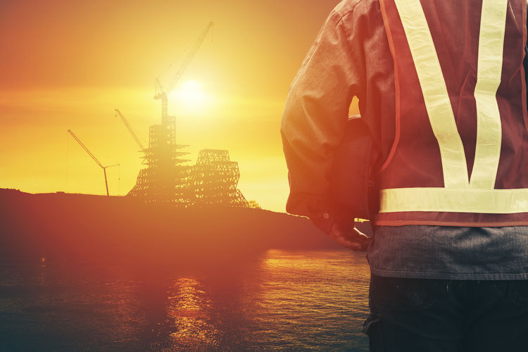Midsection Of Worker Holding Hardhat While Standing Against Incomplete Building During Sunset
