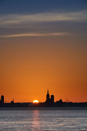 Silhouette of building by sea during sunset