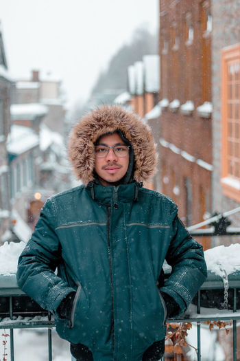 Portrait of man wearing warm clothing standing in city during winter