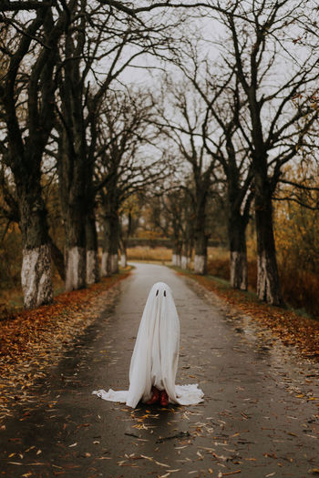Little ghost standing on the road in red boots. autumn halloween