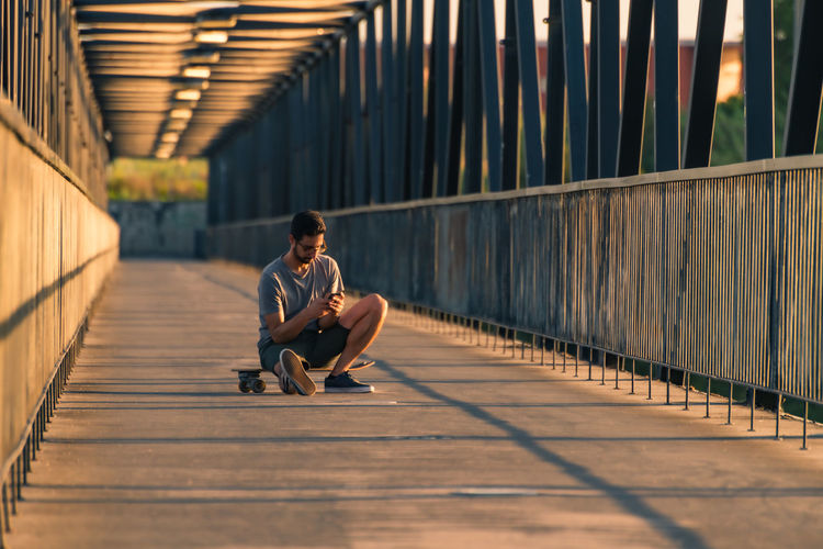 Full length of man sitting on footbridge