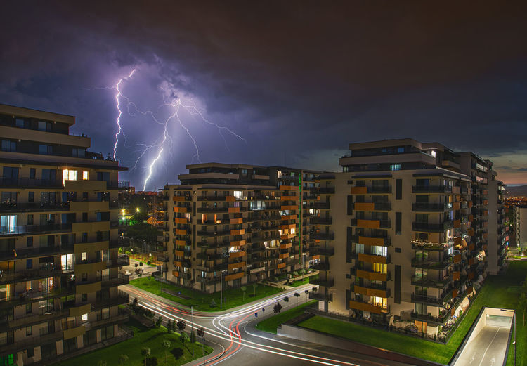 Lightning over illuminated buildings in city against sky at night