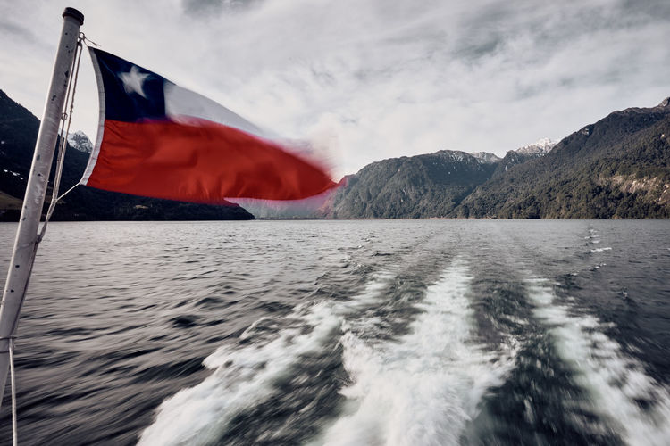 Sailing the Todos los Santos Lake... Beauty In Nature Blurred Motion Cloud - Sky Day Environment Flag Flowing Motion Mountain Mountain Range Nature No People Outdoors Patriotism Power In Nature Scenics Scenics - Nature Sea Sky Tourism Travel Destinations Wake - Water Water Waterfront Wind