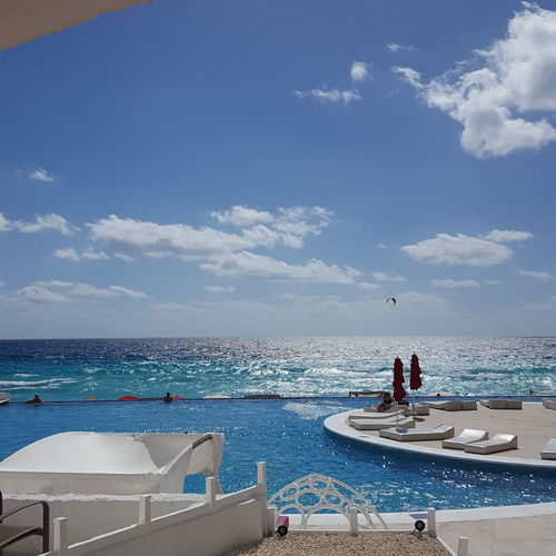 Infinity pool by sea on sunny day