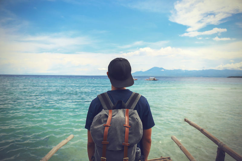 Rear View Of Man With Backpack Looking At Sea Against Sky
