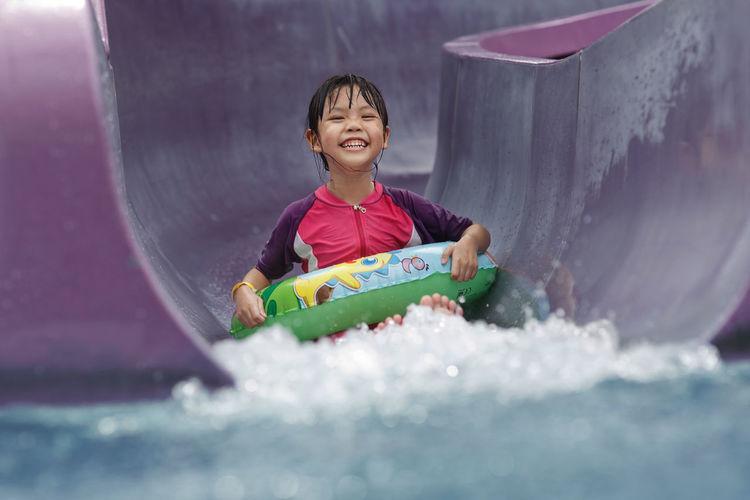 Portrait of girl sliding down in water slide at water park
