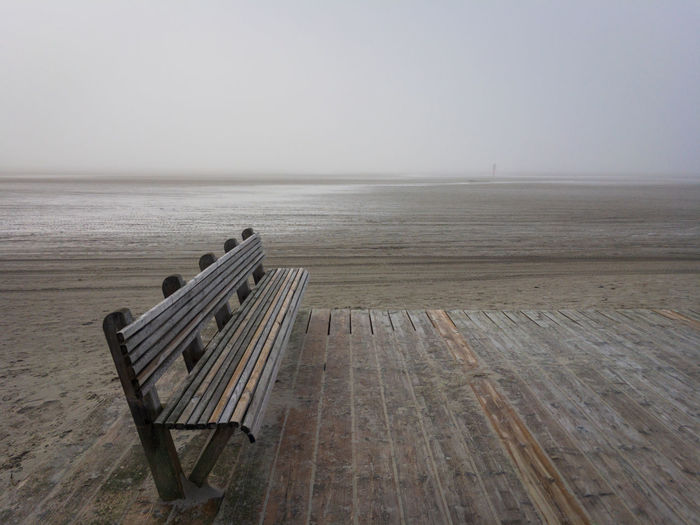 Empty bench by sea against clear sky