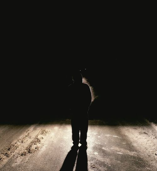 Silhouette man standing on street at night