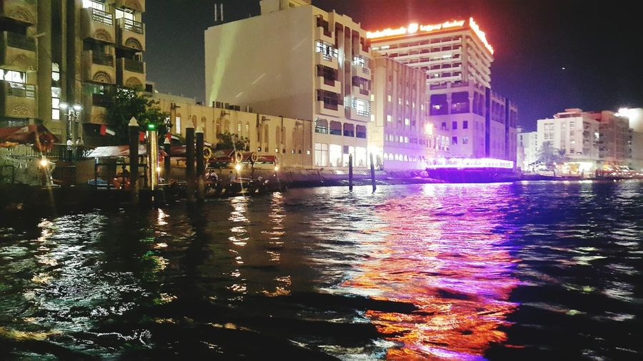 Illuminated buildings by canal in city at night
