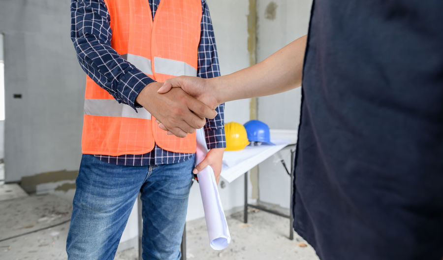 Midsection of engineer shaking hands at construction site