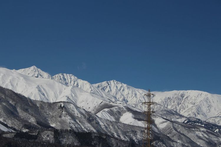 Low Angle View Of Electricity Pylon By Snow Covered Mountains Against Clear Blue Sky