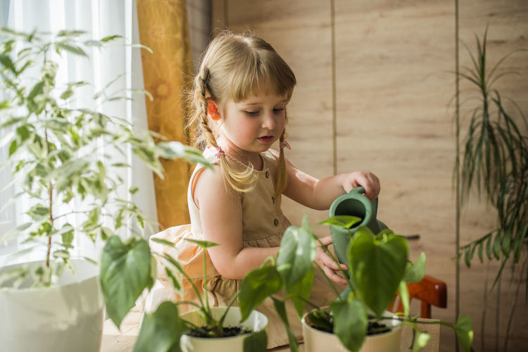 Girl watering plants at home