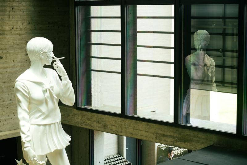 Statue of woman seen through glass window