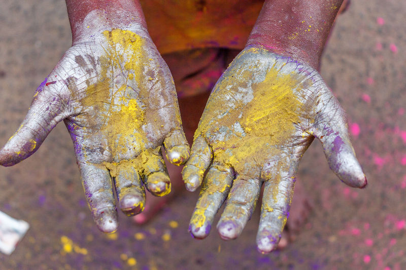 Low section of man with powder paint on hands during holi