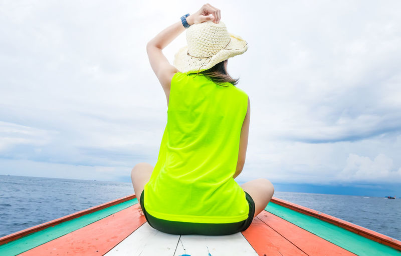 Rear view of woman wearing hat against sea against sky