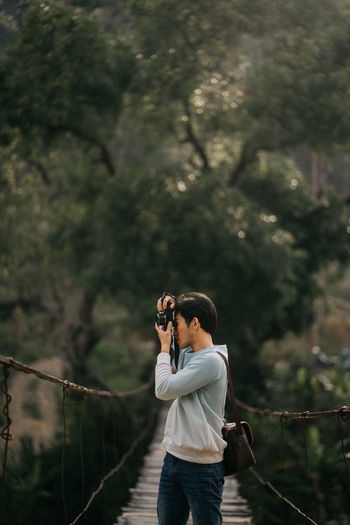 Man photographing with camera while standing by tree