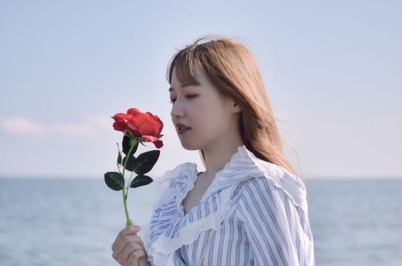 Midsection of woman holding flowering plant against sea