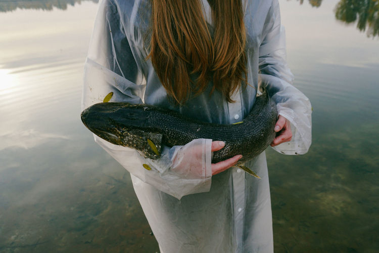 Midsection Of Young Woman Holding Fish While Standing In Lake