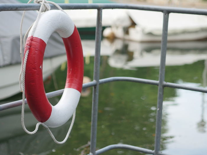 Lifebelt hanging from railing at harbor