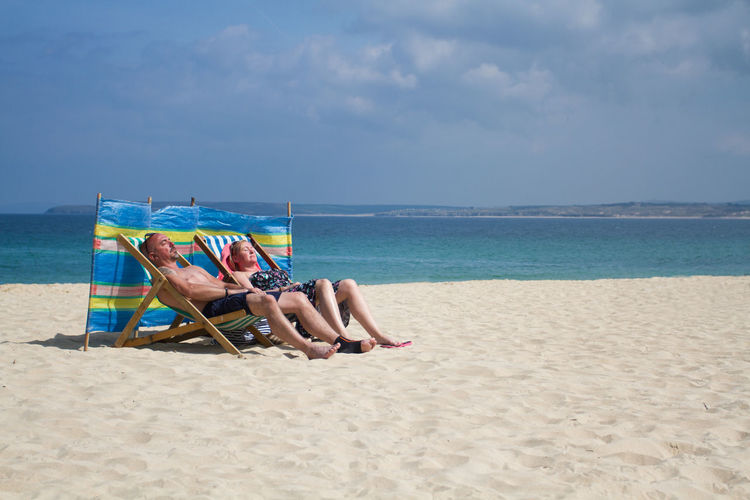 A pair of holidaymakers relaxing on a sandy beach whilst sunbathing in deckchairs and sitting behind a windbreak in a traditional, British holiday scene. Beach Beauty In Nature British Day Holidaymakers Horizon Over Water Nature Outdoors Porthminster Beach Real People Relaxation Sand Sandy Beach Scenics Sea Shore Sky St Ives Sunbathing Traditional Tranquility Vacation Vacations Water Windbreak Live For The Story