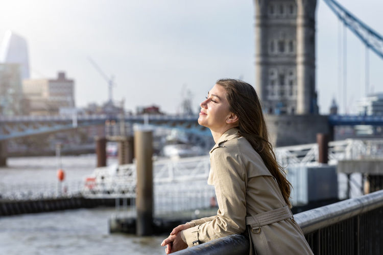 Young woman standing with eyes closed by railing in city