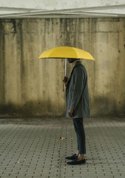 Full length of man with umbrella walking on street during rainy season