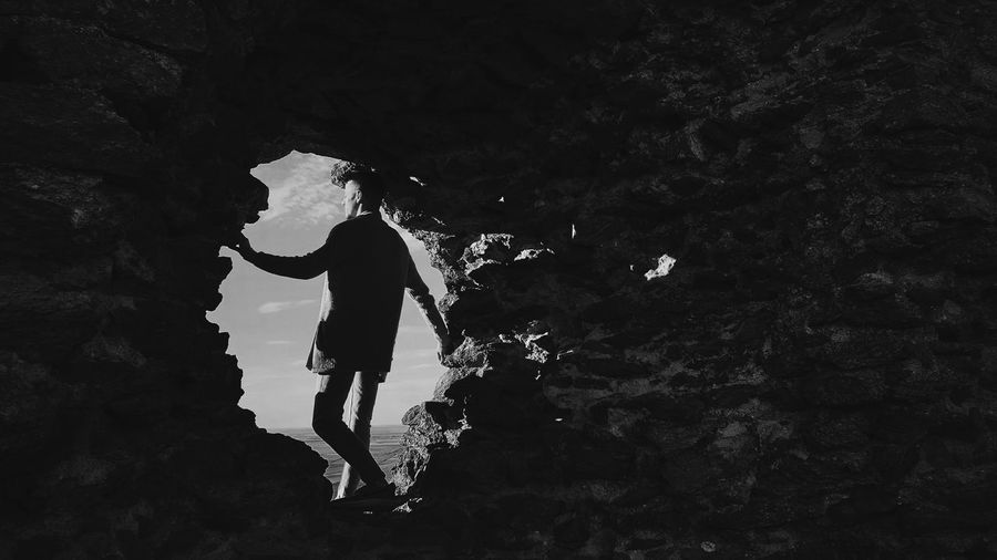 Low angle view of silhouette man standing on rock