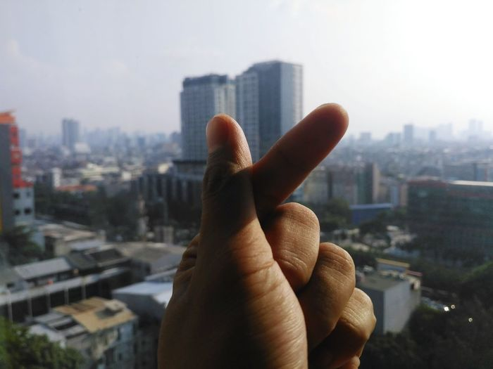 Cropped hand of person gesturing against buildings and sky in city