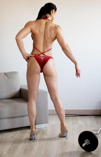 Muscular woman in bikini standing at home