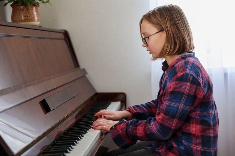 Low angle view of girl playing piano at home