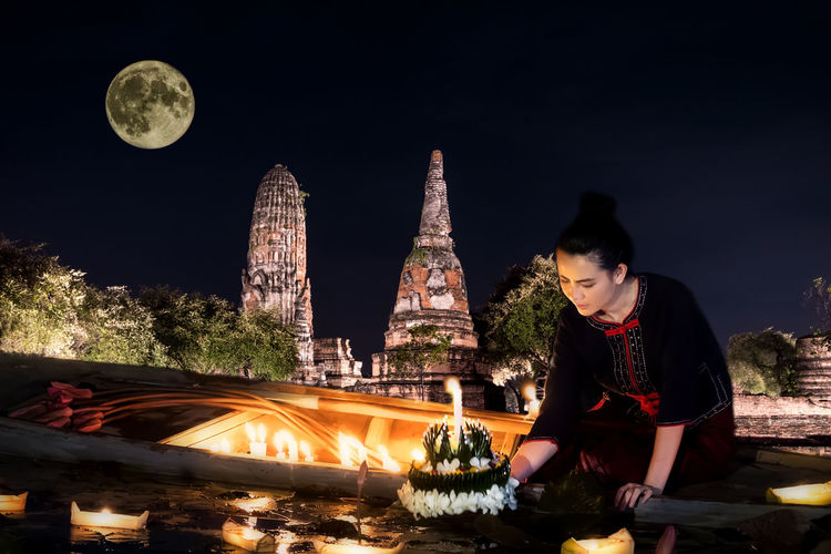 Woman standing at illuminated temple against sky at night