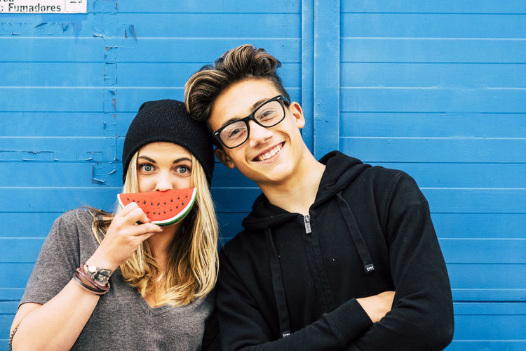Portrait of young woman with friend holding artificial watermelon against wall