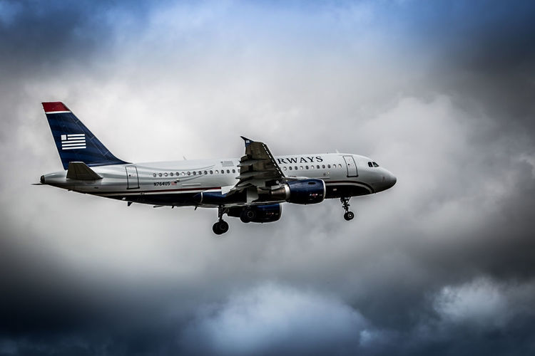 US Airways Air Vehicle Airplane Airport Airways Arts Culture And Entertainment Blue Color Commercial Airplane Depth Of Field Development Environmental Conservation Journey Low Angle View Mid-air Mode Of Transport No Limits No People On The Move Outdoors Runway Selective Focus Technology Tilt-shift Transportation